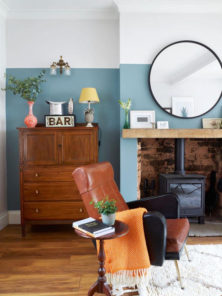 Mid-sized eclectic medium tone wood floor and brown floor living room photo in Other with a bar, blue walls and a wood stove