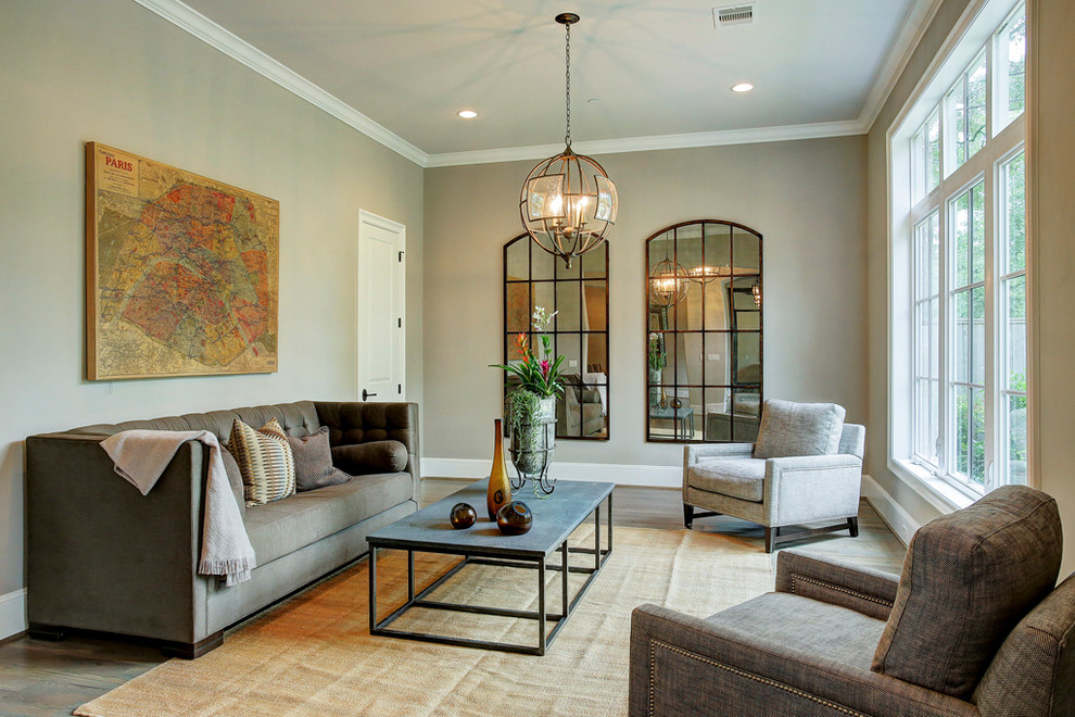 Example of a transitional formal and enclosed medium tone wood floor living room design in Houston with gray walls and a wall-mounted tv