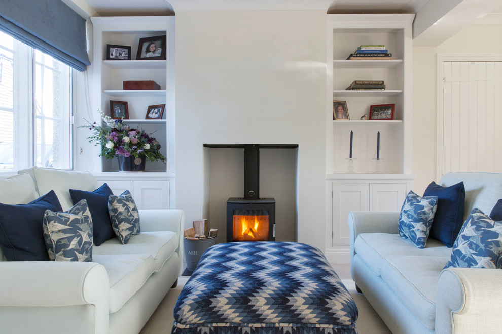 Example of a small beach style carpeted living room design in Hampshire with beige walls and a wood stove