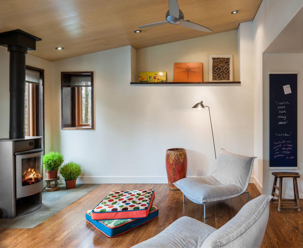 Example of a mid-sized transitional formal and loft-style light wood floor and brown floor living room design in Philadelphia with a wood stove, black walls, a metal fireplace and a wall-mounted tv