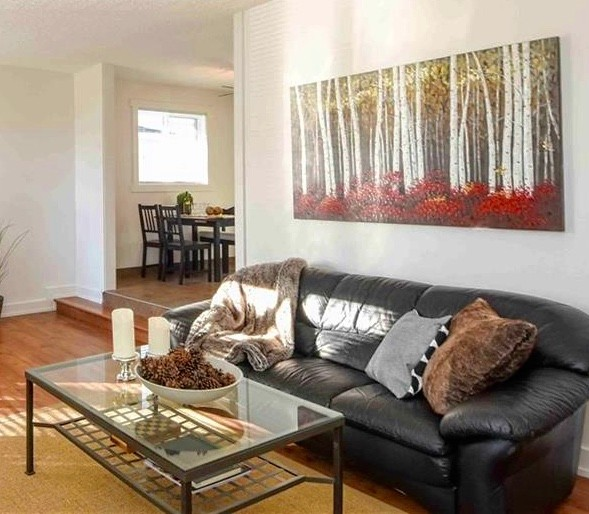 Example of a mid-sized transitional enclosed brown floor living room design in Calgary with white walls