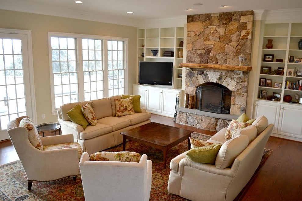 Inspiration for a mid-sized timeless open concept dark wood floor and brown floor living room remodel in Other with beige walls, a standard fireplace, a stone fireplace and a tv stand