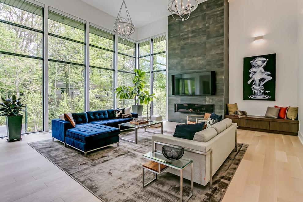 Diseño de salón abierto, contemporáneo, extra grande, con paredes blancas, suelo de madera clara, chimenea lineal, marco de chimenea de piedra, televisor colgado en la pared y suelo beige