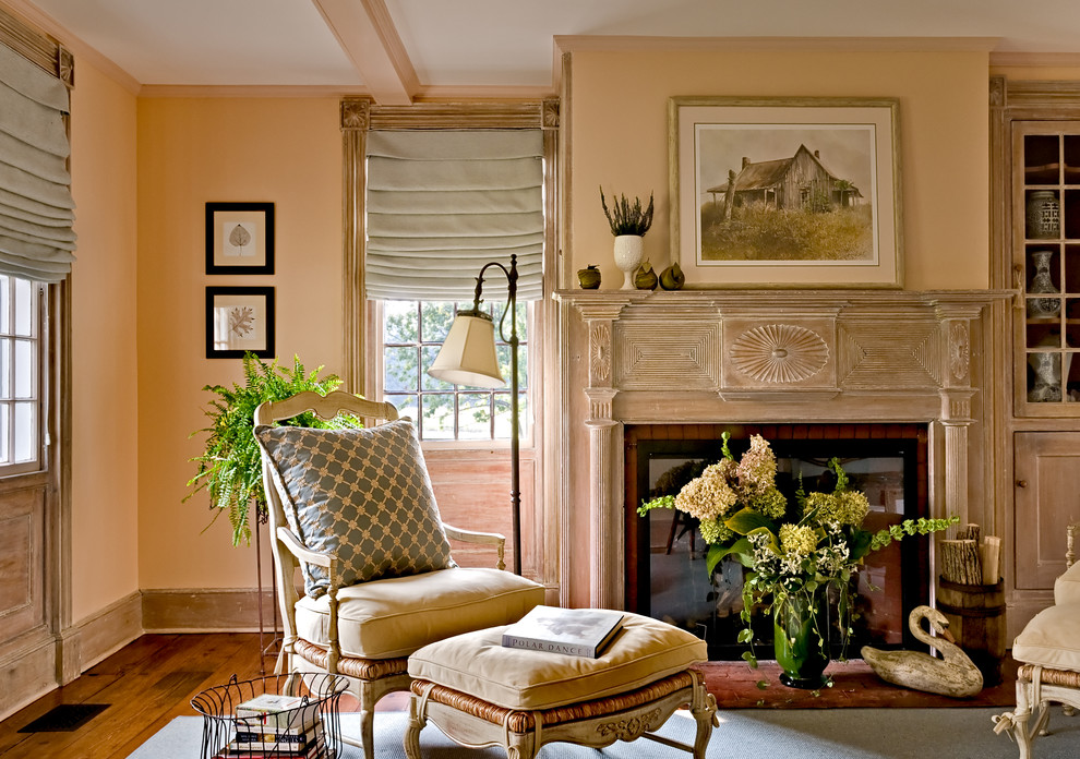Example of a classic medium tone wood floor living room design in New York with a standard fireplace