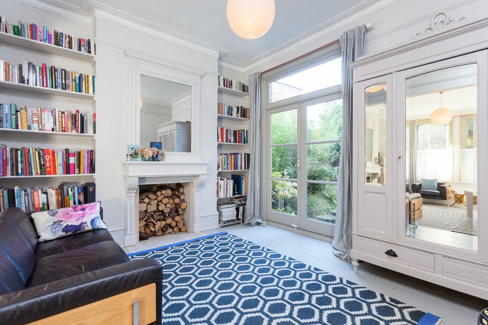 Danish enclosed painted wood floor living room library photo in London with gray walls and a standard fireplace