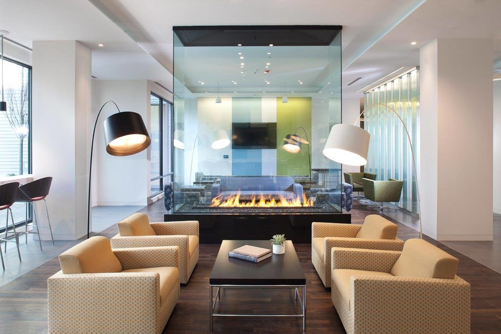 Example of a trendy formal and open concept dark wood floor living room design in Boston with white walls and a two-sided fireplace
