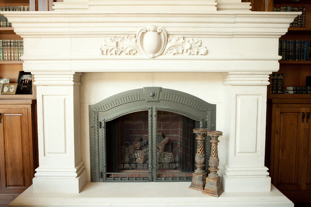 Cast stone fireplace surround with over mantel and hearth - enclosed by wood book cases