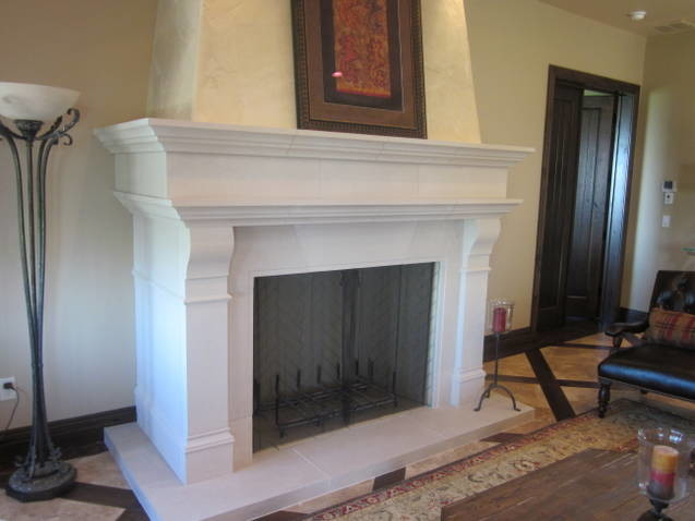 Cast stone fireplace surround that wraps around wall pop out.