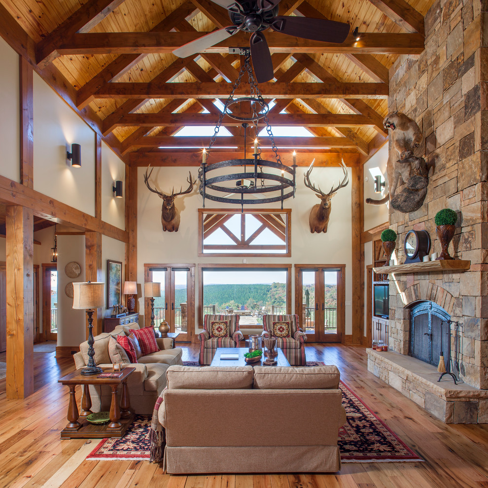 Huge mountain style open concept medium tone wood floor living room photo in Other with a standard fireplace, a stone fireplace, a media wall and white walls