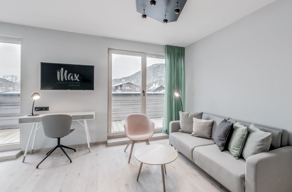 Small danish light wood floor living room photo in Manchester with white walls