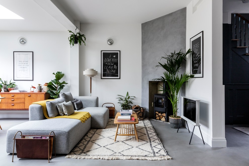 Inspiration for a mid-sized scandinavian open concept concrete floor and gray floor living room remodel in London with white walls, a wood stove and a tv stand