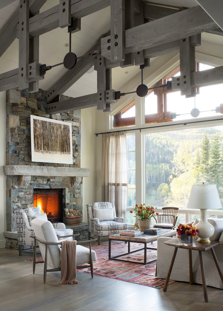 Example of a mountain style medium tone wood floor living room design in Seattle with white walls, a standard fireplace and a stone fireplace