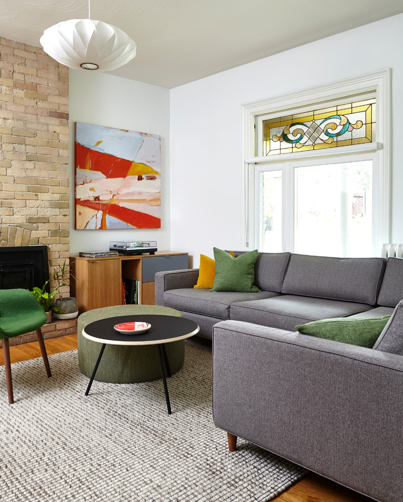 Example of a mid-sized danish enclosed medium tone wood floor and brown floor living room design in Toronto with white walls, a standard fireplace, a brick fireplace and a concealed tv
