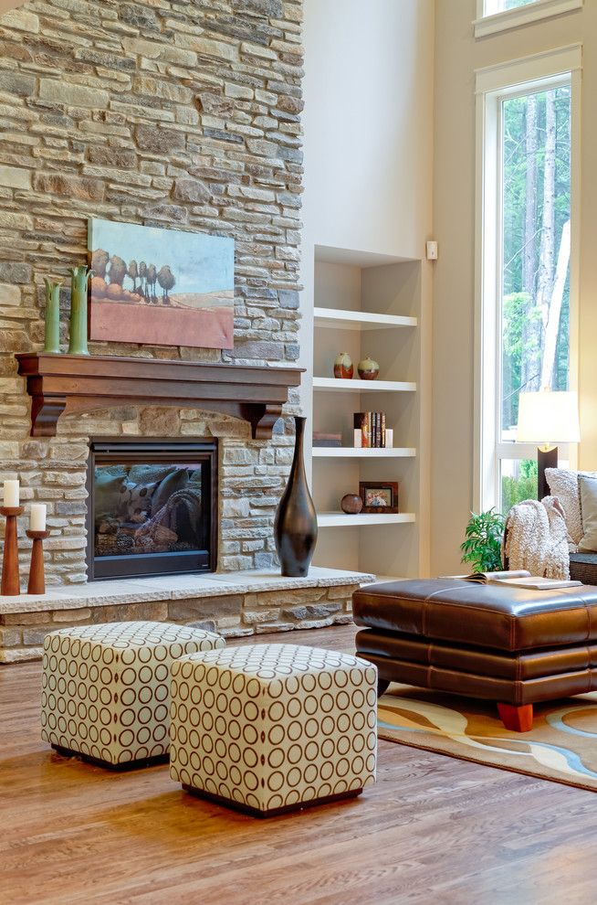 Example of a classic living room design in Seattle with a standard fireplace and a stone fireplace