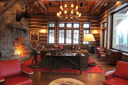 a red carpet and red armchairs in a rustic cabin space