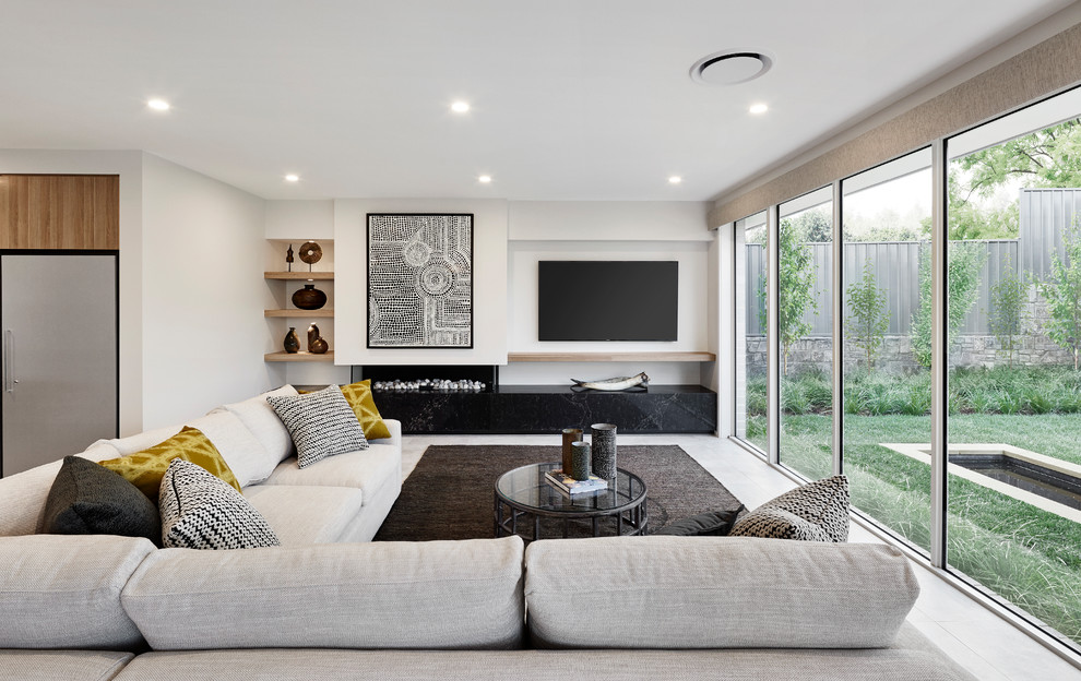 Photo of a contemporary open concept living room in Sydney with white walls, a ribbon fireplace, a plaster fireplace surround, a wall-mounted tv and white floor.