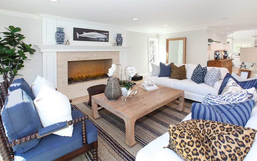 Example of a coastal open concept light wood floor living room design in Orange County with gray walls, a standard fireplace, a brick fireplace and no tv