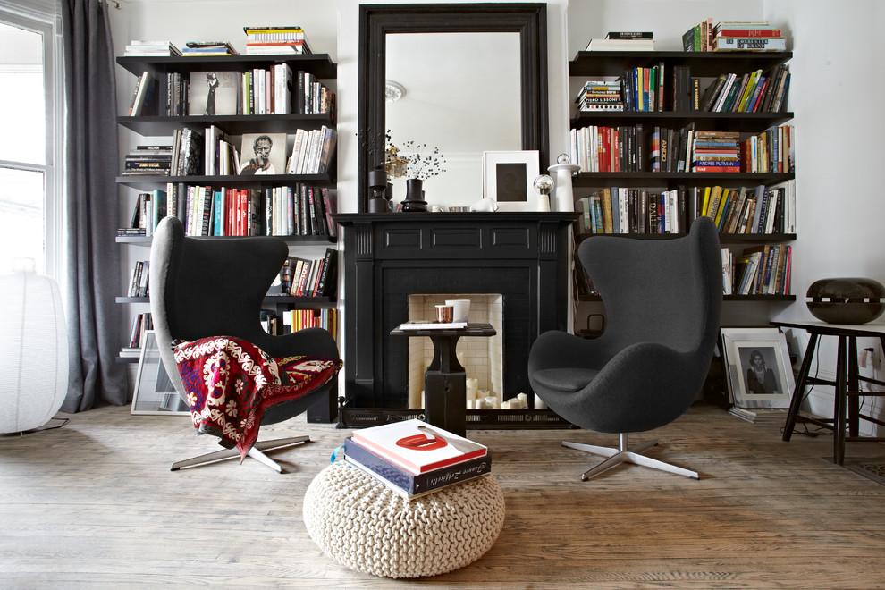 Modelo de biblioteca en casa contemporánea, sin televisor, con paredes blancas, suelo de madera en tonos medios, todas las chimeneas, marco de chimenea de madera y cortinas