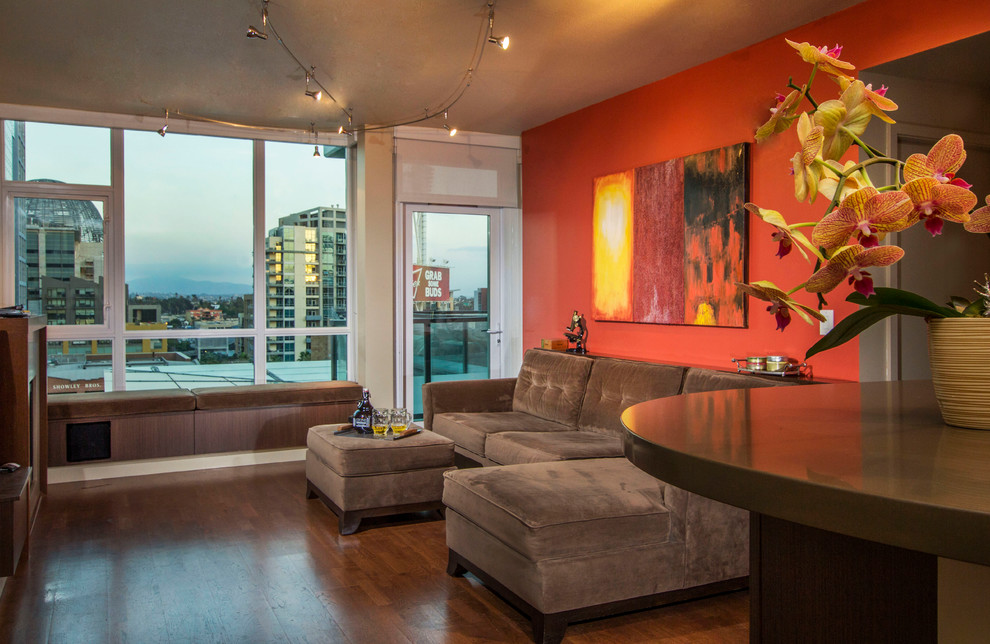 Inspiration for a small contemporary open concept medium tone wood floor living room remodel in San Diego with orange walls, a standard fireplace, a stone fireplace and a wall-mounted tv