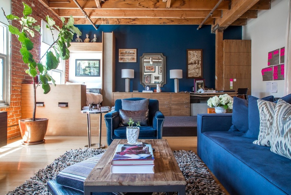 Inspiration for an industrial open concept light wood floor living room remodel in Los Angeles with blue walls