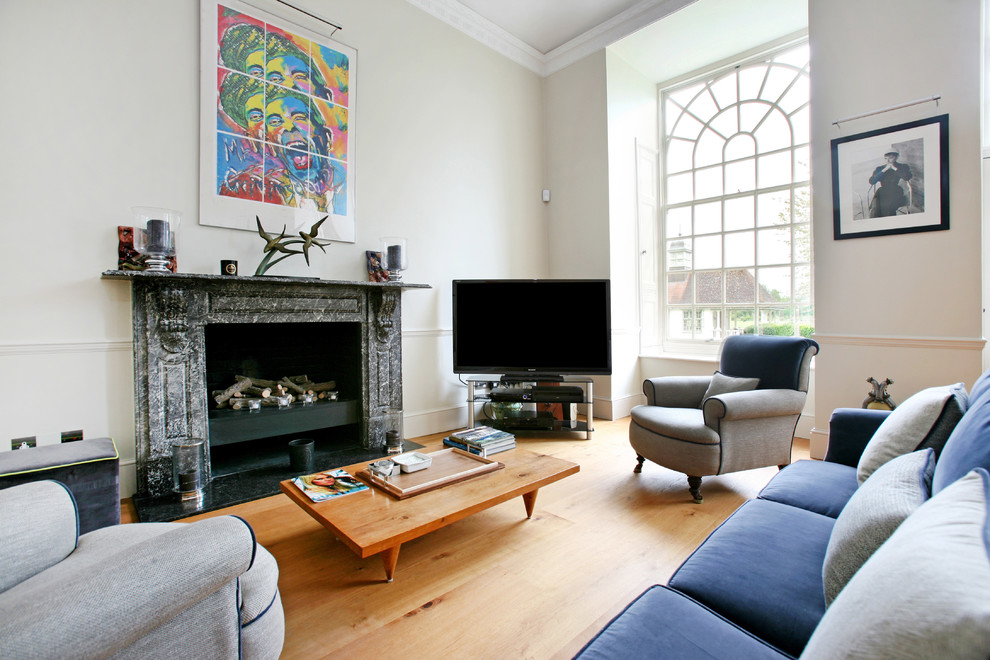 Example of a classic living room design in London with white walls