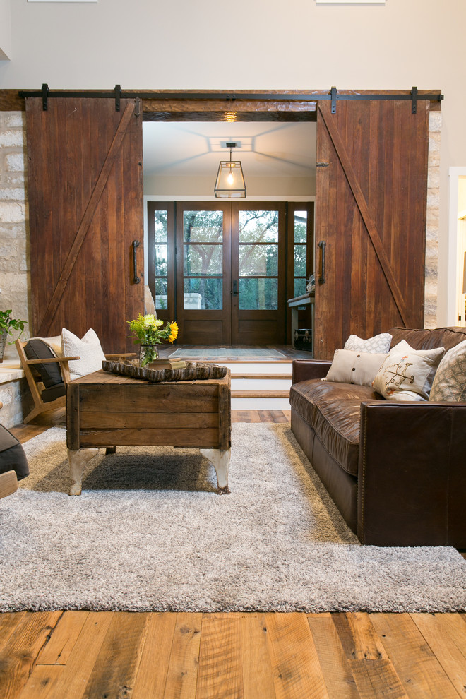 Cottage open concept medium tone wood floor living room photo in Austin with beige walls, a standard fireplace and a stone fireplace