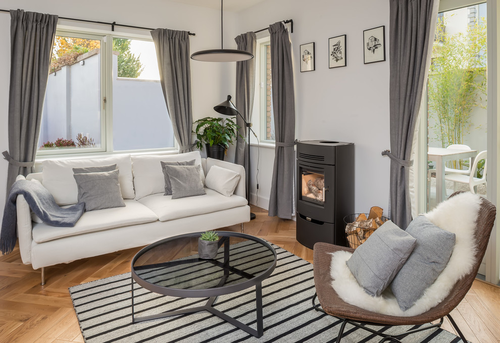 Mid-sized danish enclosed beige floor living room photo in Dublin with white walls, a wood stove and a metal fireplace