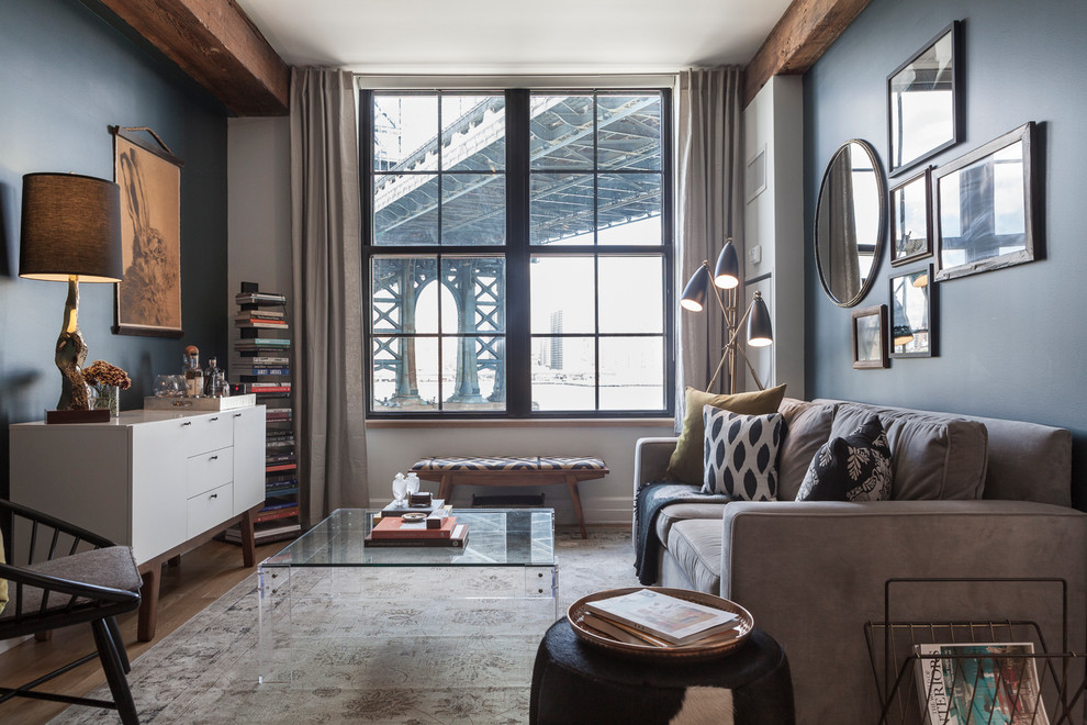 Example of a transitional light wood floor living room library design in New York with blue walls, no fireplace and no tv