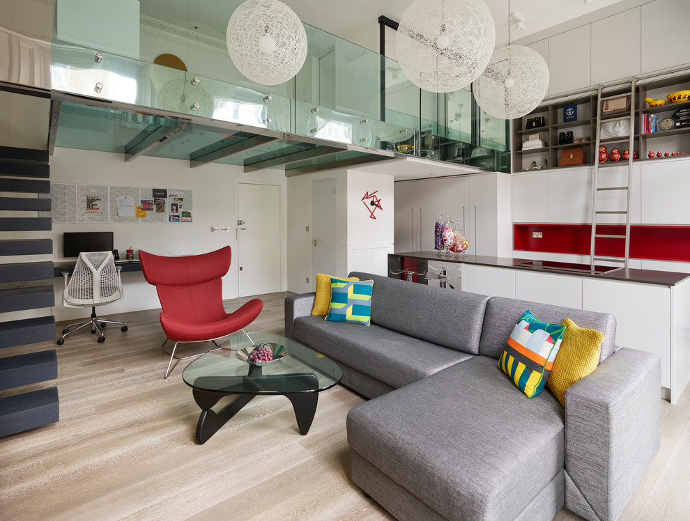 Design ideas for a small contemporary open plan living room in London with white walls and light hardwood flooring.