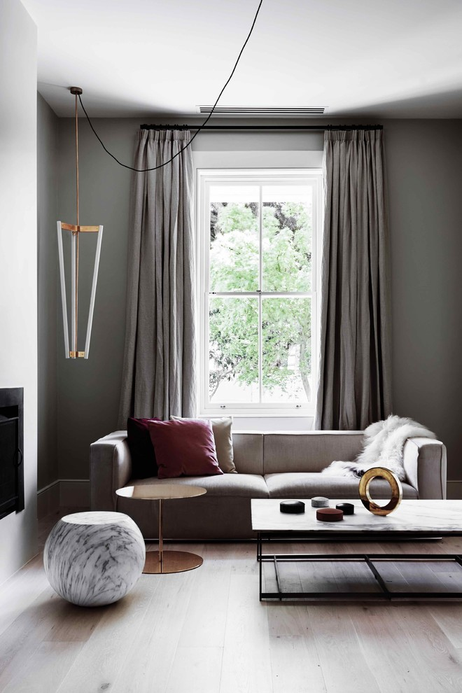 Example of a mid-sized trendy open concept light wood floor living room design in Melbourne with gray walls and a standard fireplace