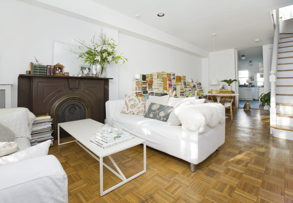 Living room - eclectic medium tone wood floor living room idea in New York with white walls and a standard fireplace