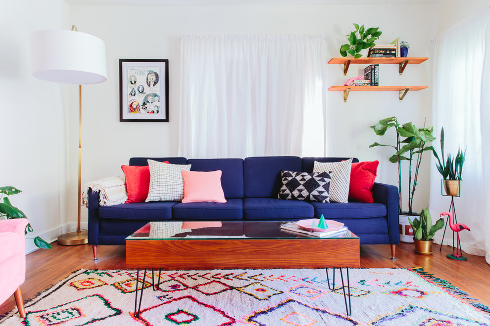 Inspiration for a mid-sized eclectic formal medium tone wood floor living room remodel in Los Angeles with white walls, no fireplace and no tv
