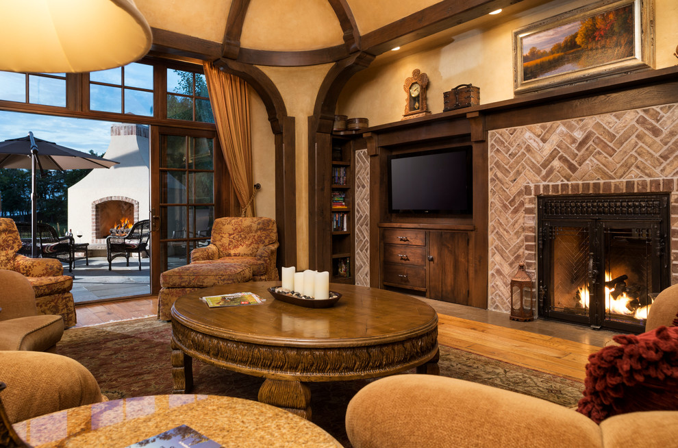 Large elegant open concept medium tone wood floor living room photo in Minneapolis with a standard fireplace, a brick fireplace, beige walls and a concealed tv