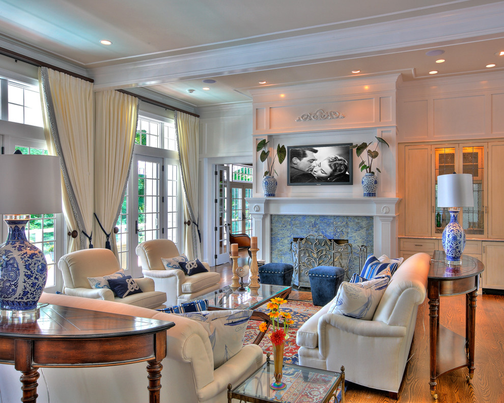 Mid-sized elegant enclosed and formal medium tone wood floor living room photo in New York with a standard fireplace, a stone fireplace, a wall-mounted tv and white walls