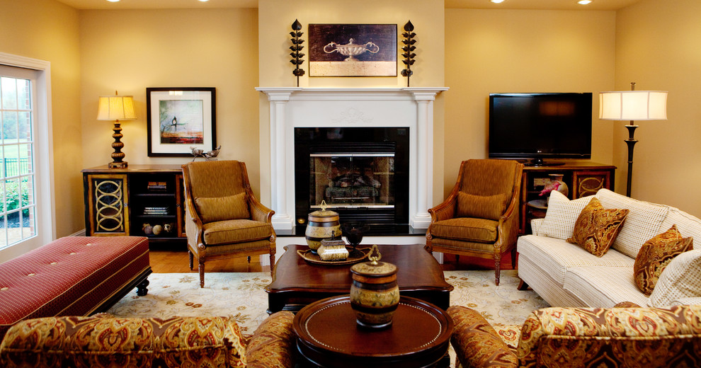 Mid-sized elegant formal and open concept medium tone wood floor and brown floor living room photo in Birmingham with beige walls, a standard fireplace, a tile fireplace and a tv stand
