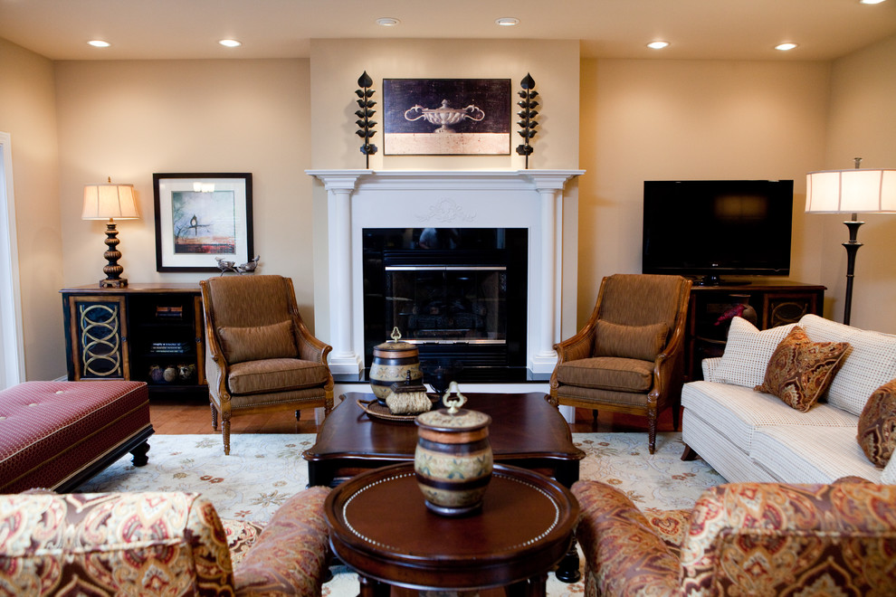 Living room - mid-sized traditional formal and open concept medium tone wood floor and brown floor living room idea in Birmingham with beige walls, a standard fireplace, a tile fireplace and a tv stand