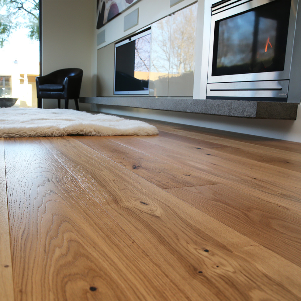 Inspiration for a modern light wood floor living room remodel in Melbourne with a concrete fireplace