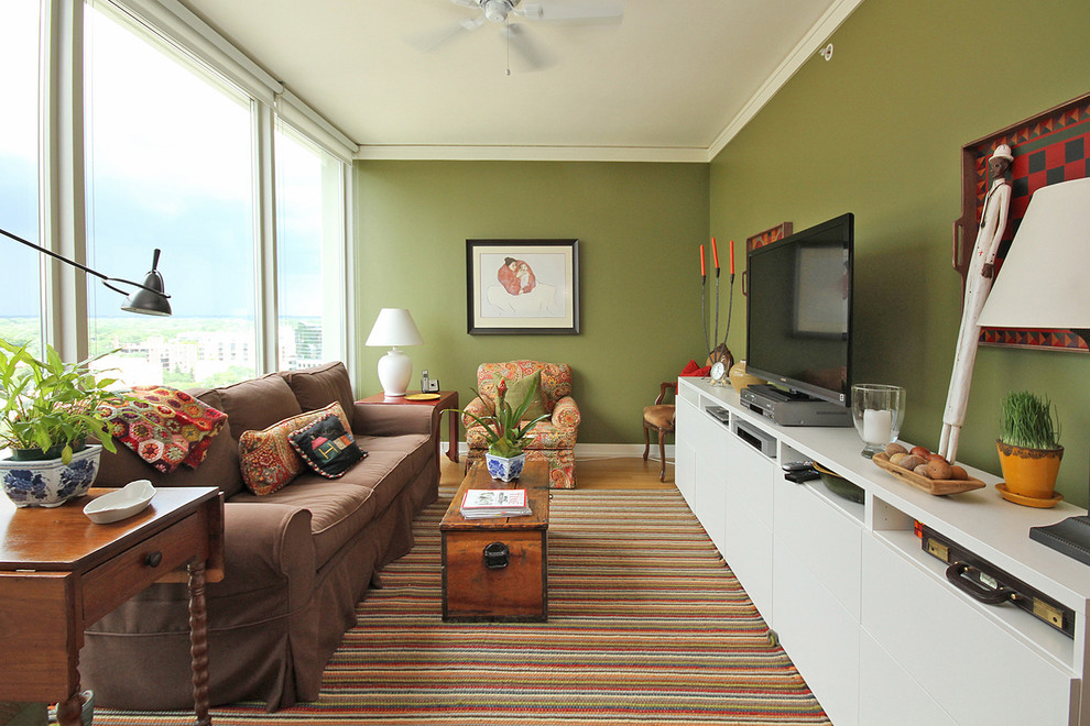 Inspiration for an eclectic living room remodel in Chicago with green walls and a tv stand