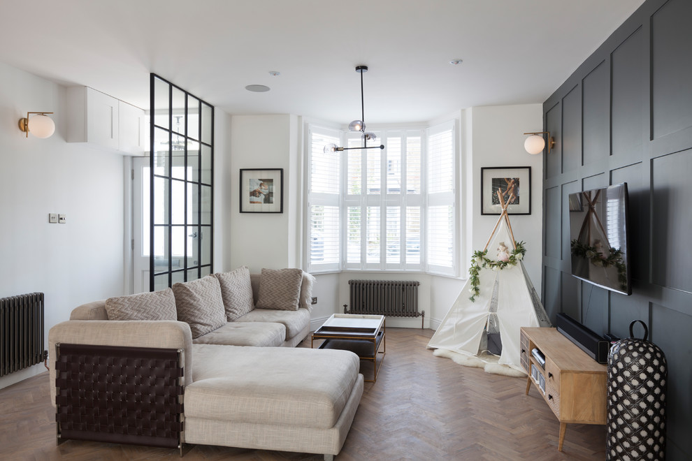 Living room - small transitional enclosed light wood floor living room idea in London with white walls and a wall-mounted tv