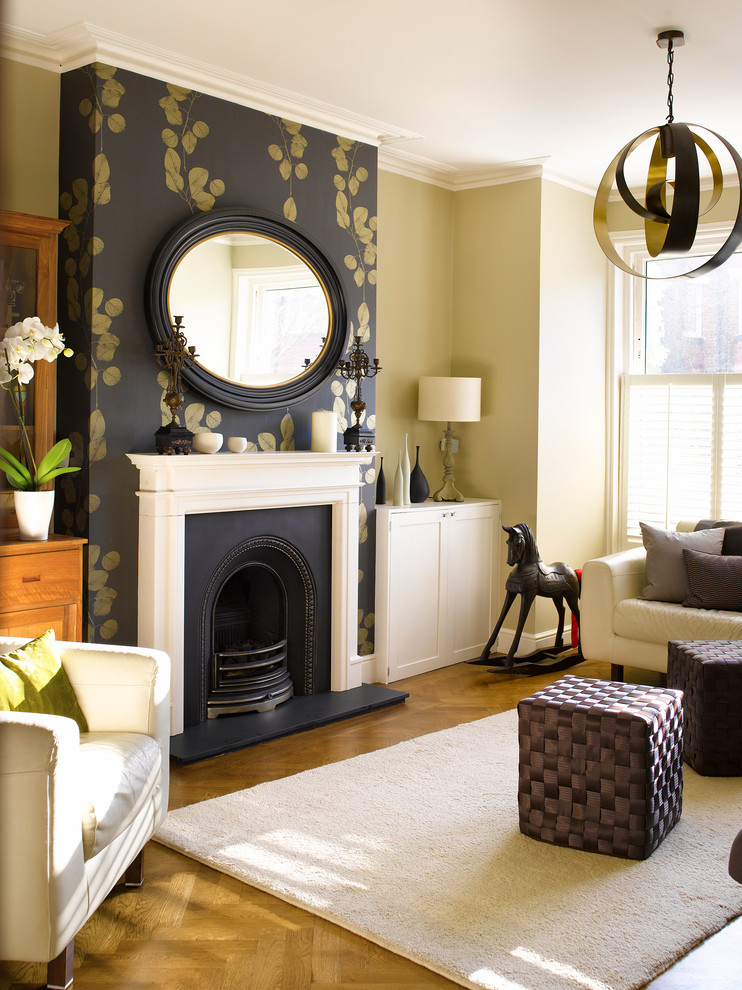 Example of a large transitional formal medium tone wood floor living room design in London with a standard fireplace, no tv and beige walls