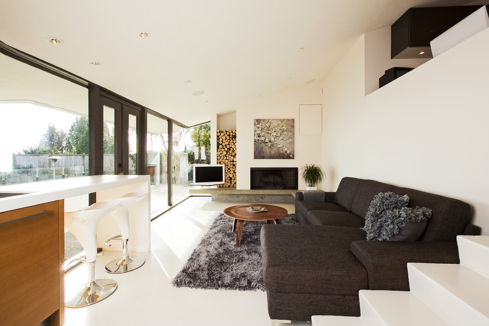 Living room - mid-sized modern concrete floor and white floor living room idea in Vancouver with white walls, a standard fireplace and a tv stand