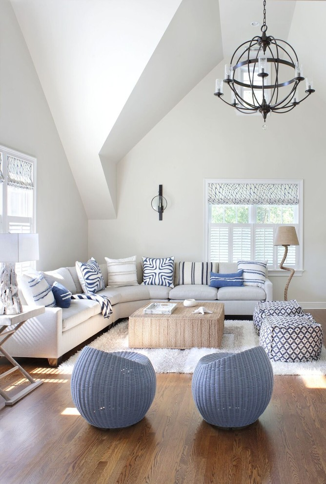 Beach style medium tone wood floor and brown floor living room photo in New York with white walls