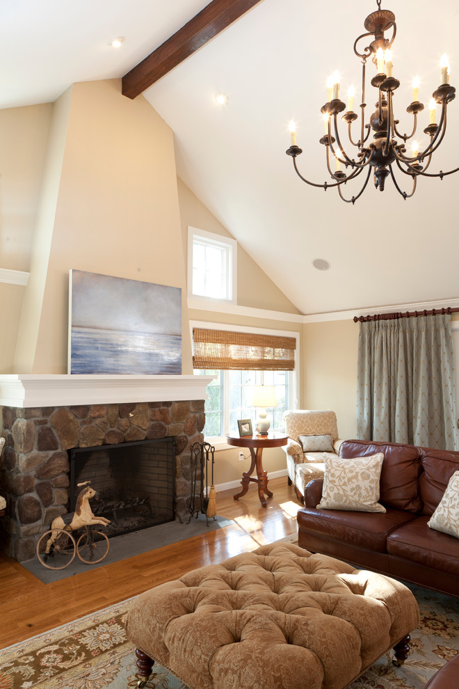 Example of a large classic open concept medium tone wood floor and brown floor living room design in Salt Lake City with beige walls, a standard fireplace, a stone fireplace and a wall-mounted tv