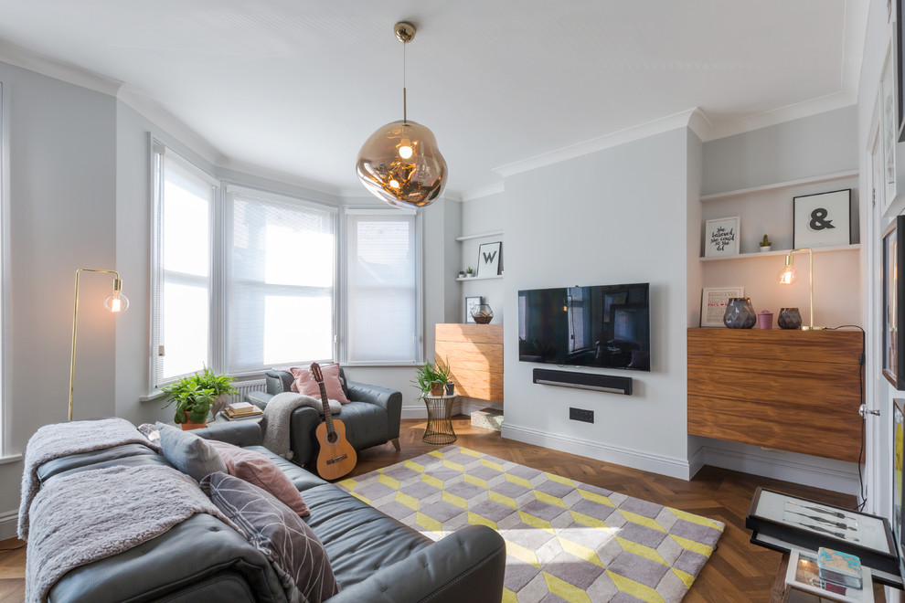 Mid-sized trendy enclosed medium tone wood floor living room photo in London with gray walls and a wall-mounted tv