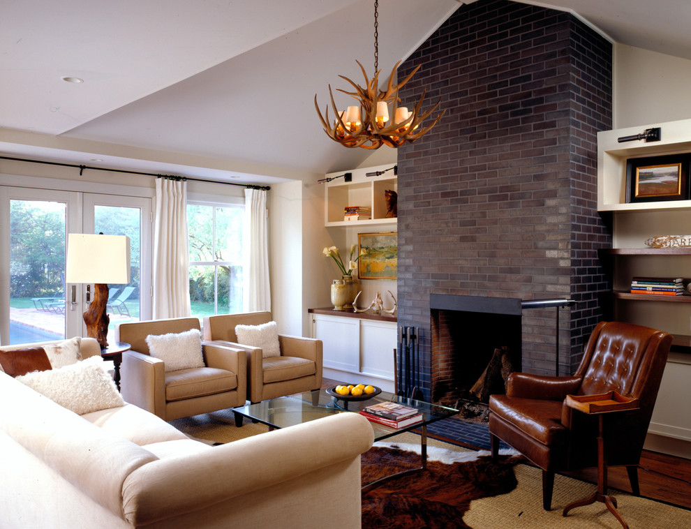 Country living room photo in New York with a brick fireplace