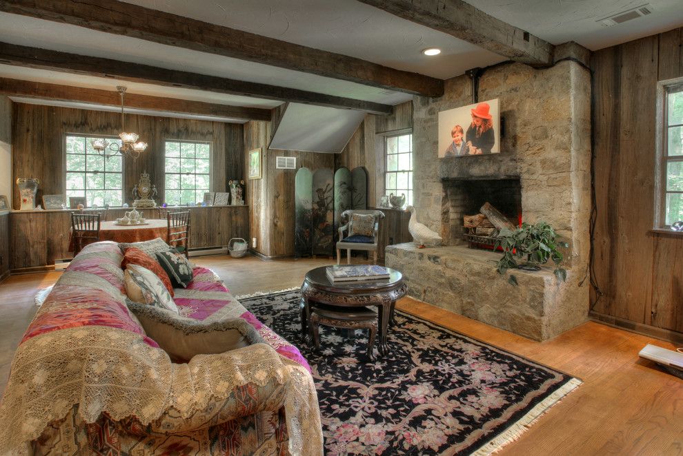 Living room - cottage living room idea in New York with a standard fireplace, a stone fireplace and brown walls