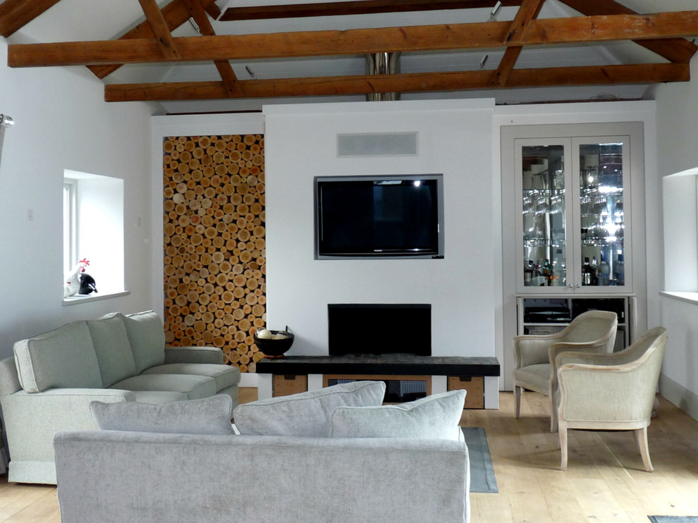 Trendy light wood floor living room photo in Gloucestershire with white walls, a standard fireplace and a plaster fireplace