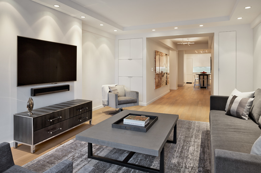 Example of a mid-sized trendy enclosed light wood floor living room design in New York with white walls, a wall-mounted tv and no fireplace