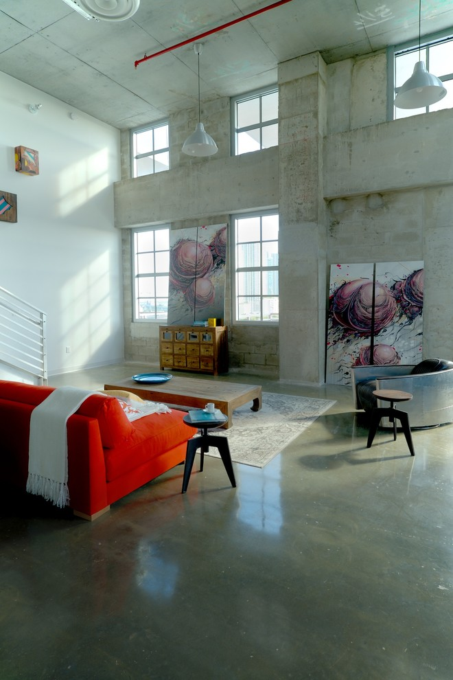 Living room - large industrial open concept concrete floor living room idea in Miami with white walls