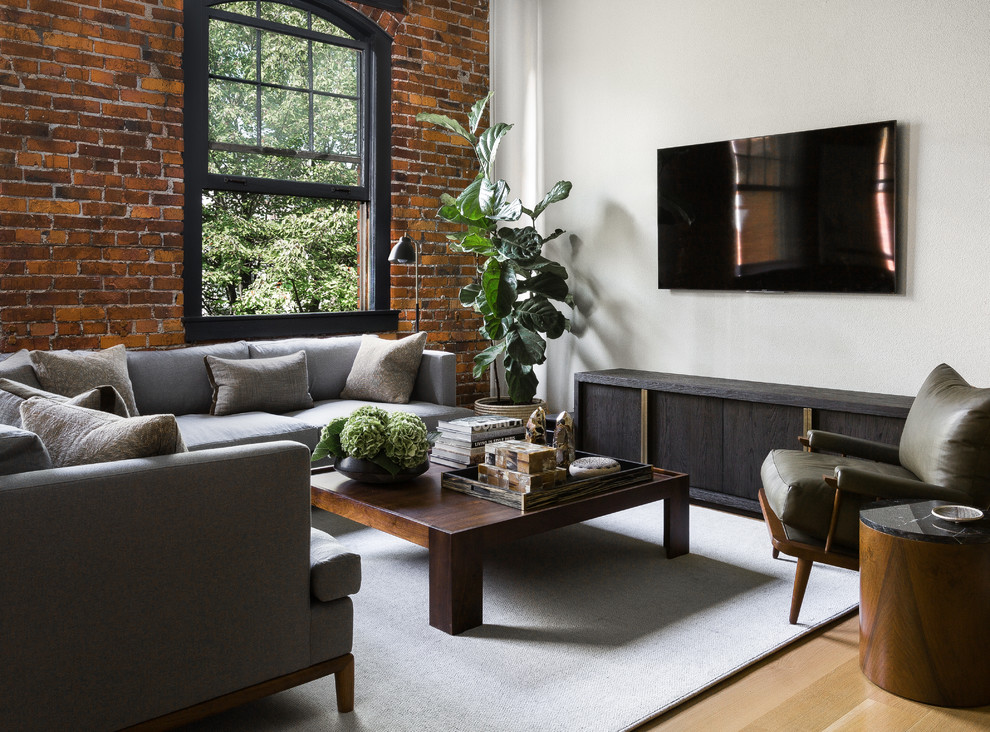 Example of a transitional light wood floor and beige floor living room design in Seattle with white walls and a wall-mounted tv